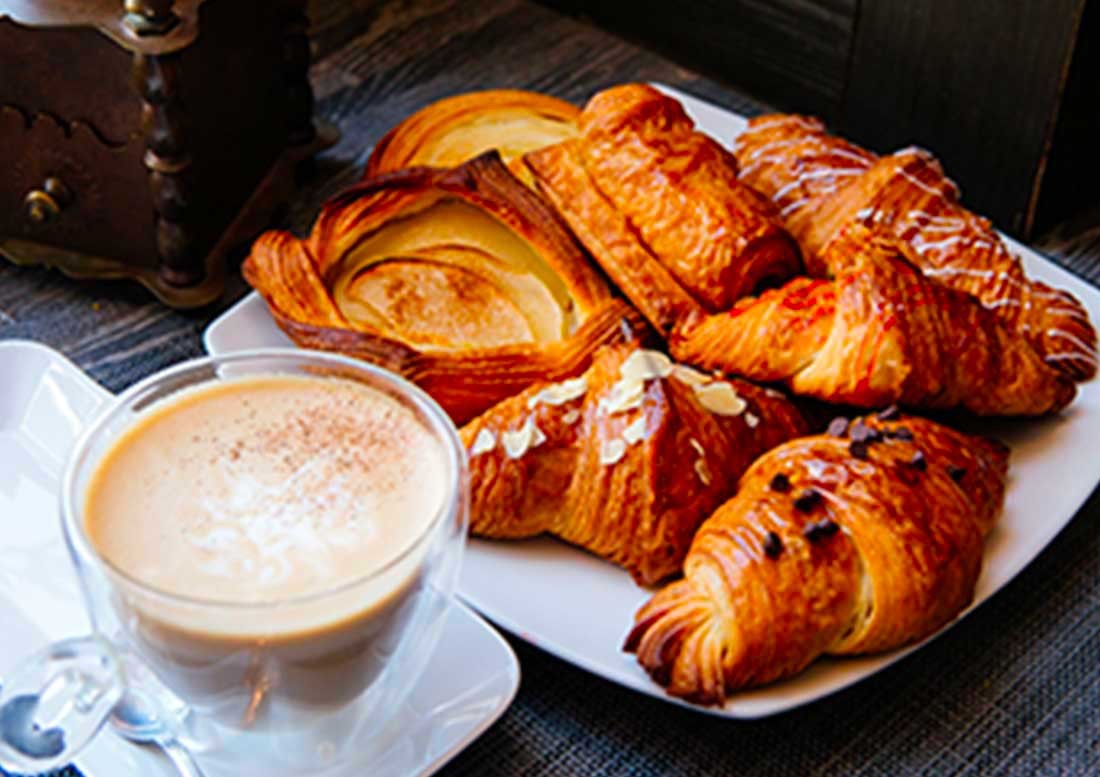 Croissant alla crema e al cioccolato con tazza di cappuccino
